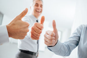 Cheerful business people thumbs up